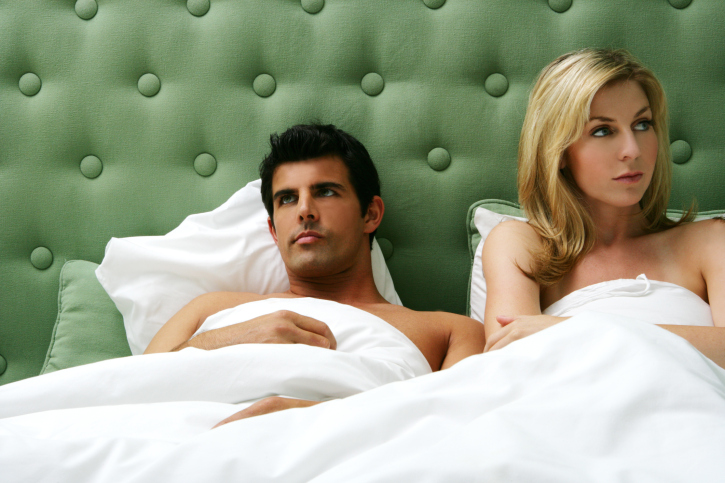 Young couple ignoring each other in bed.