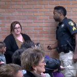 Поліцейський просить покинути зал вчительку Дейшу Харгрейв